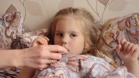 Petite fille malade se situant dans son lit et mère vérifiant la température de sa fille malade dans sa bouche banque de vidéos