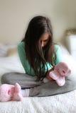 Petite fille malheureuse dans des pantoufles pelucheuses Photographie stock