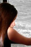 Petite fille malheureuse par la fenêtre, vue d'océan grise Image stock