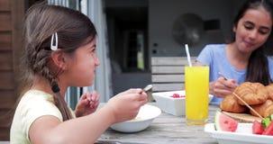 Petite fille mangeant des cornflakes dehors banque de vidéos