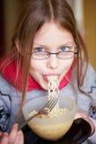 Petite fille mangeant des nouilles images stock