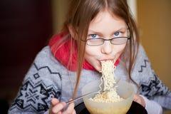 Petite fille mangeant des nouilles Image libre de droits