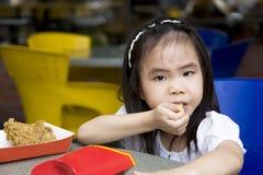 Petite fille mangeant des pommes frites Images stock
