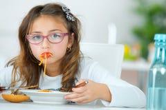 Petite fille mangeant des spaghetti à la maison photos libres de droits