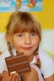 Petite fille mangeant du chocolat Photos libres de droits