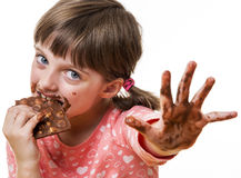 Petite fille mangeant du chocolat Image stock