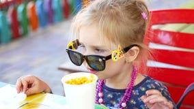 Petite fille mangeant du maïs de nourriture de rue en parc d'été, concept de nourriture de voyage banque de vidéos