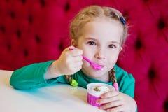 Petite fille mangeant la crème glacée en café Image stock