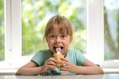 Petite fille mangeant la crème glacée tout en se reposant à une table, l'espace libre Photographie stock