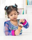 Petite fille mangeant la crême glacée Photos libres de droits