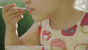 Petite fille mangeant la crême glacée Une petite fille mange une crême glacée 4K banque de vidéos