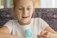 Petite fille mangeant la cr?me glac?e bleue dans un caf? Fille ravie avec la cr?me glac?e  Petite fille adorable mangeant la cr?m image libre de droits