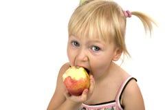 Petite fille mangeant la pomme rouge Image libre de droits