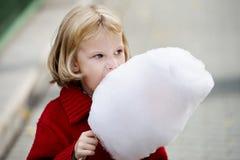 Petite fille mangeant la sucrerie de coton Photos libres de droits
