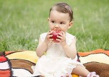 Petite fille mangeant une pomme Image libre de droits