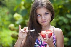 Petite fille mangeant une tranche de tomate Photos libres de droits