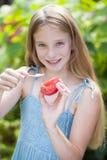 Petite fille mangeant une tranche de tomate Photographie stock libre de droits