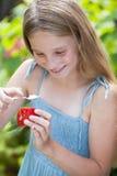 Petite fille mangeant une tranche de tomate Images stock