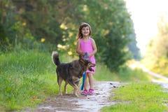 Petite fille marchant avec le chien Photo libre de droits