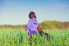 Petite fille marchant avec le chien Photos stock