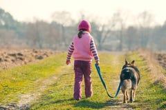 Petite fille marchant avec le chien Photographie stock libre de droits