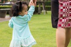 Petite fille marchant avec sa mère pour rentrer à la maison Image stock