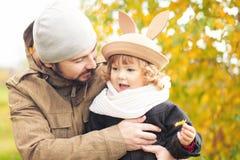 Petite fille marchant avec son père en parc, jour d'automne Photos stock