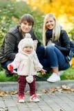 Petite fille marchant en parc d'automne avec ses parents photographie stock libre de droits