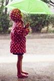 Petite fille marchant sous la pluie Photographie stock