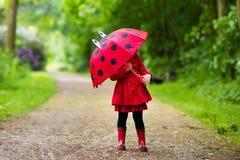Petite fille marchant sous la pluie Photographie stock libre de droits