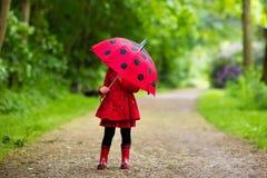 Petite fille marchant sous la pluie Photo stock