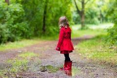 Petite fille marchant sous la pluie Photos libres de droits