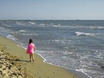 Petite fille marchant sur la plage Images stock