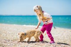 Petite fille marchant sur la plage avec un terrier de chiot Images libres de droits