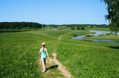Petite fille marchant sur le champ de nouveau à l'appareil-photo Images stock