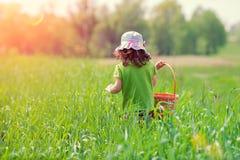 Petite fille marchant sur le champ vert Image stock