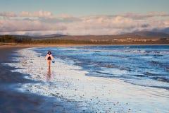 Petite fille marchant sur le rivage au coucher du soleil Photographie stock