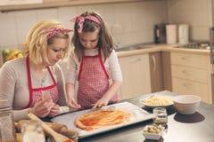 Petite fille mettant le sésame sur le bord de la pâte de pizza Photo libre de droits