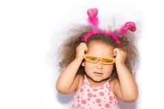 Petite fille mettant les lunettes de soleil oranges Photographie stock libre de droits