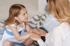 Petite fille mettant ses paumes sur des mains de sa mère Photo stock