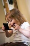 Petite fille mettant sur le renivellement Photos stock
