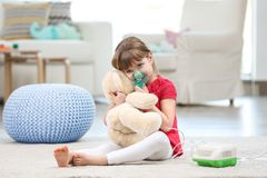Petite fille mignonne à l'aide du nébuliseur d'asthme à la maison image libre de droits