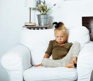 Petite fille mignonne à la maison s'asseyant dans la chaise, peo de sourire de mode de vie photo libre de droits