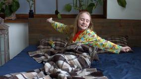 Petite fille mignonne étirant ses bras après éveillé banque de vidéos