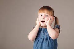 Petite fille mignonne étonnante sur le fond gris Photographie stock libre de droits