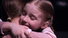 Petite fille mignonne étreignant étroitement sa mère après la longue séparation, sourire sur le visage clips vidéos
