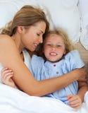 Petite fille mignonne étreignant avec sa mère Photo libre de droits