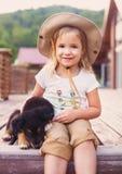 Petite fille mignonne étreignant le chiot de chien Images stock