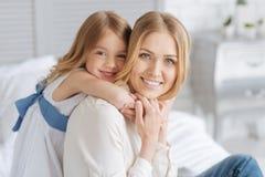 Petite fille mignonne étreignant sa mère Image stock