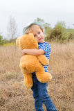 Petite fille mignonne étreignant un grand ours de nounours Photos libres de droits